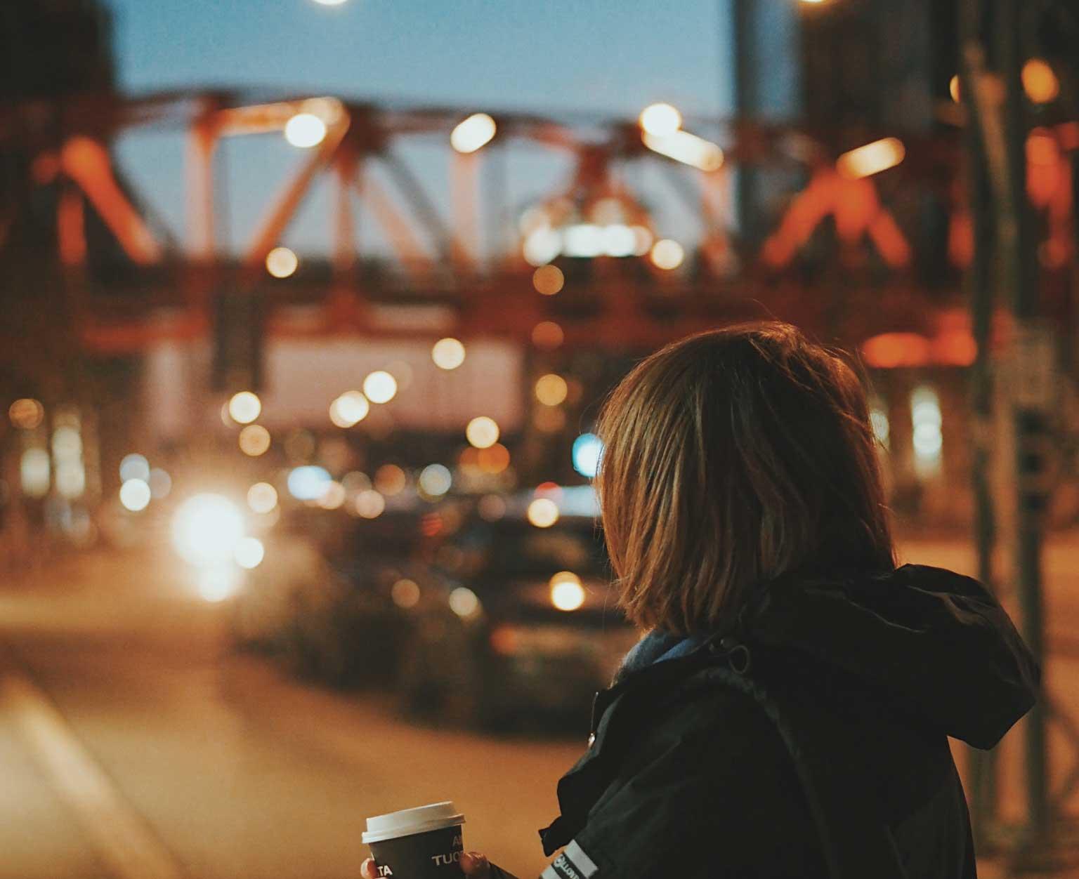 Nuori nainen seisoo kahvikupin kanssa kadulla. On ilta.